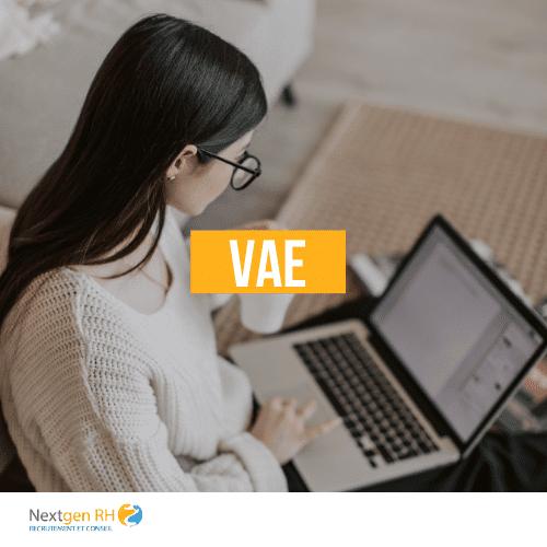 """On peut voir écrit """"VAE"""" au centre de l'image avec en arrière plan une fille sur son ordinateur entrain de travailler."""